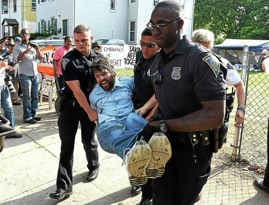 Gregory Williams of the Amistad Catholic Worker House is carried away after being arrested by police at a city-owned property on Howard Avenue in New Haven Friday, a day after the group erected a homeless tent compound. Photo: Peter Casolino — New Haven Register