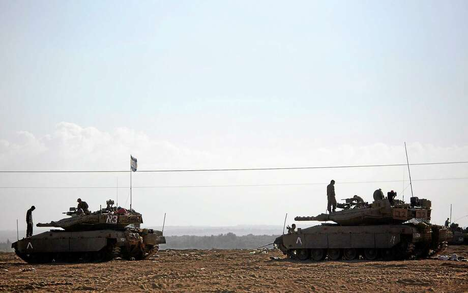Israeli soldiers work on their tanks near the Israel and Gaza border on July 25, 2014. Early Friday, Israeli warplanes struck tens of houses throughout the Gaza Strip as international efforts continue to broker a cease fire in the 18 day-old war. Photo: AP Photo/Dusan Vranic   / AP