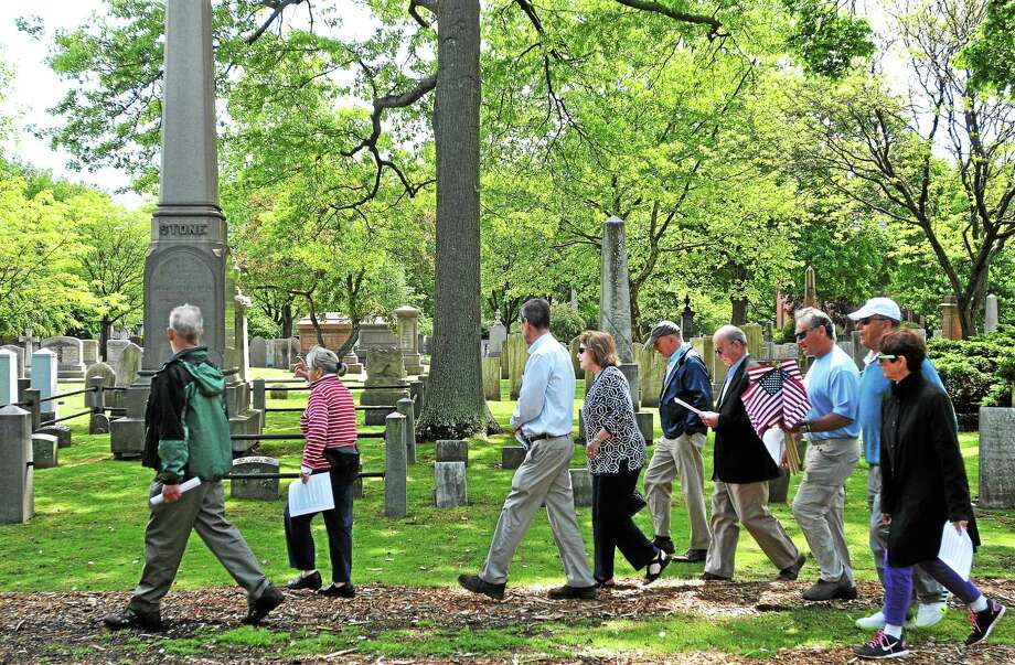 Members of the New Haven Civil War reading group walk as they were placing American flags on Civil War Soldiers (mostly from Yale) at the Grove Street Cemetery for Memorial Day. Volunteers planted around 30 flags to commemorate the fallen from the 1800's at the cemetery. Photo: (Peter Casolino — New Haven Register)