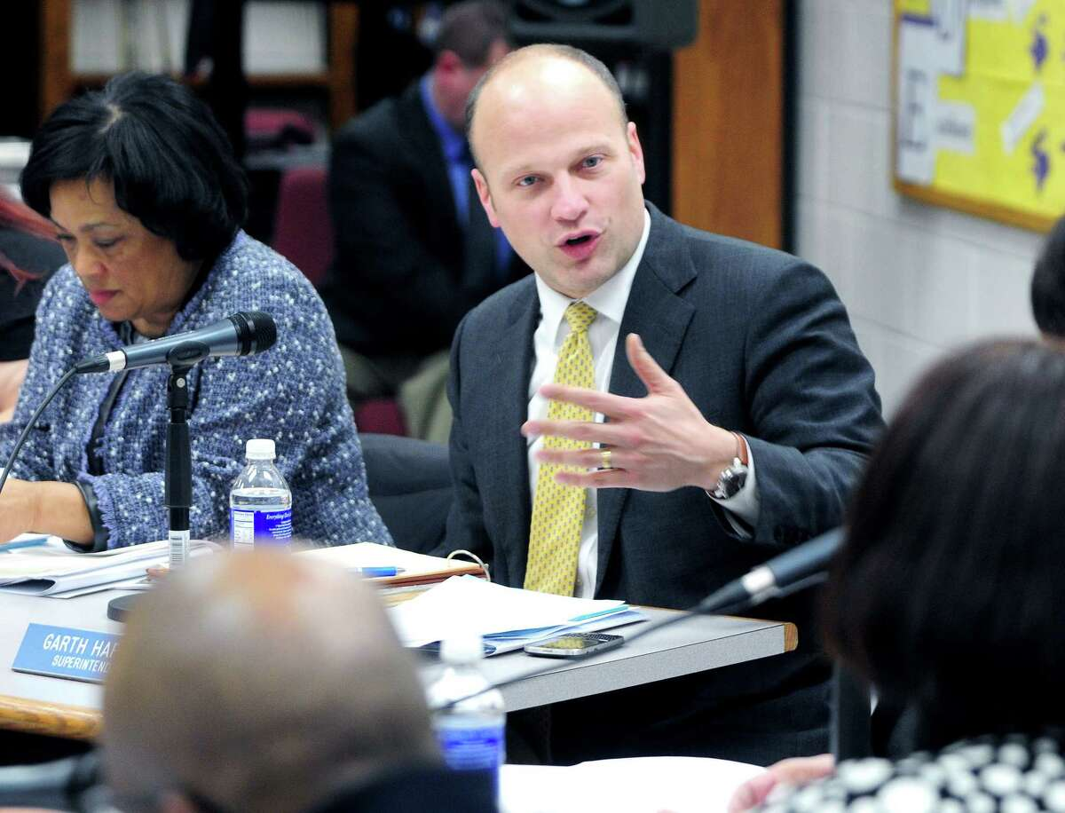 New Haven Superintendent of Schools Garth Harries, center, speaks at a Board of Education meeting at Hill Regional Career High School in February.