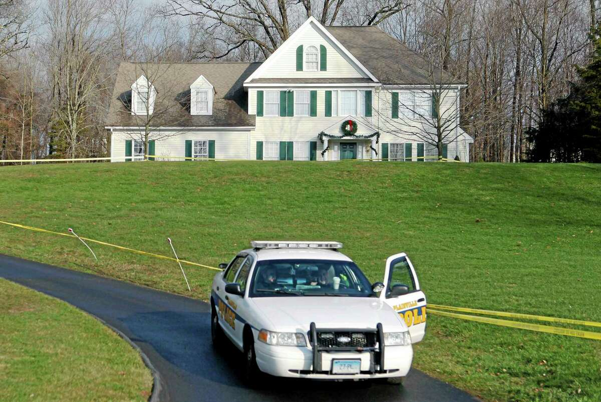 In this Dec. 18, 2012, photo, a police cruiser sits in the driveway as crime scene tape surrounds the home of Nancy Lanza in Newtown.