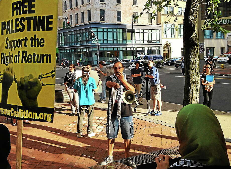 "Demonstrators gather on the southeast corner of the New Haven Green Thursday night to protest Israel's recent treatment of Palestine. Activist Norm Clement uses a megaphone to rally the group, chanting, ""when people occupy, resistance is justified."" Photo: Evan Lips — New Haven Register"