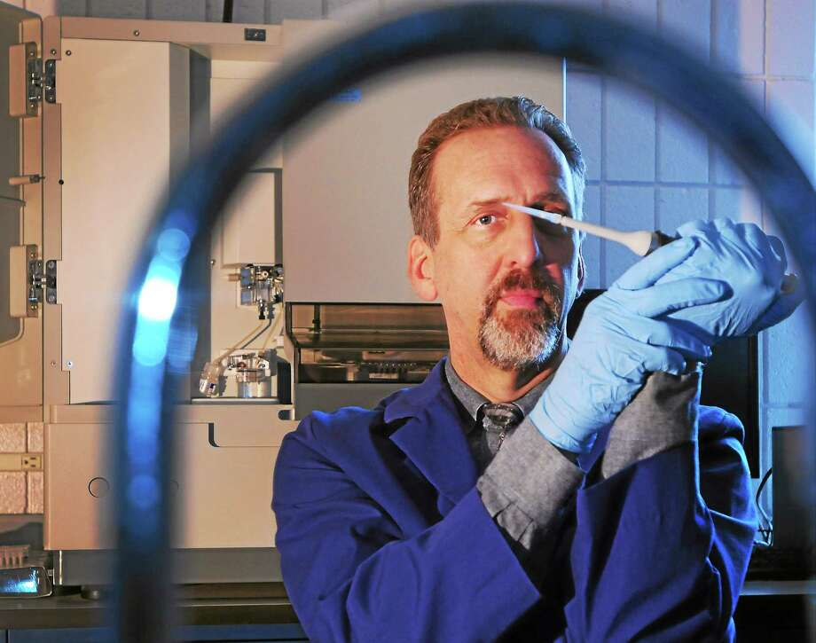 (Peter Hvizdak-New Haven Register)  Timothy M. Palmbach, University of New Haven Chair & Associate Professor of the Forensic Science Department and the Executive Director of the Institute of Forensic Science in a UNH Forensic Science lab at UNH Wednesday, March 19, 2014. Palmbach is in an expert using DNA to end sex trafficking around the world,  holds a micro pipettor as he sits in front of  Cappillary Electro Phoresis Instrument, aka  DNA Analyzer,that is used as a major step in processing the biological fingerprint of DNA. Photo: New Haven Register / ©Peter Hvizdak /  New Haven Register