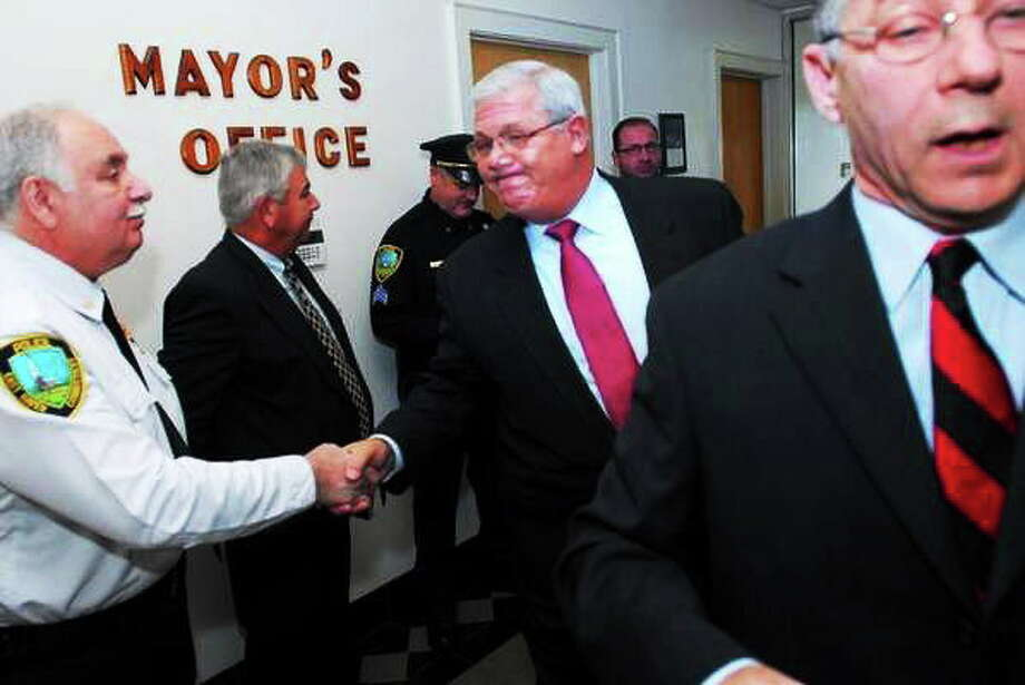 East Haven Police Chief Leonard Gallo (center) shakes hands with Inspector Gaetano Nappi (left) after East Haven Mayor Joe Maturo, Jr., (right) reinstated Gallo was to his former position at a press conference at East Haven Town Hall on 11/29/2011.Photo by Arnold Gold/New Haven Register Photo: Journal Register Co.