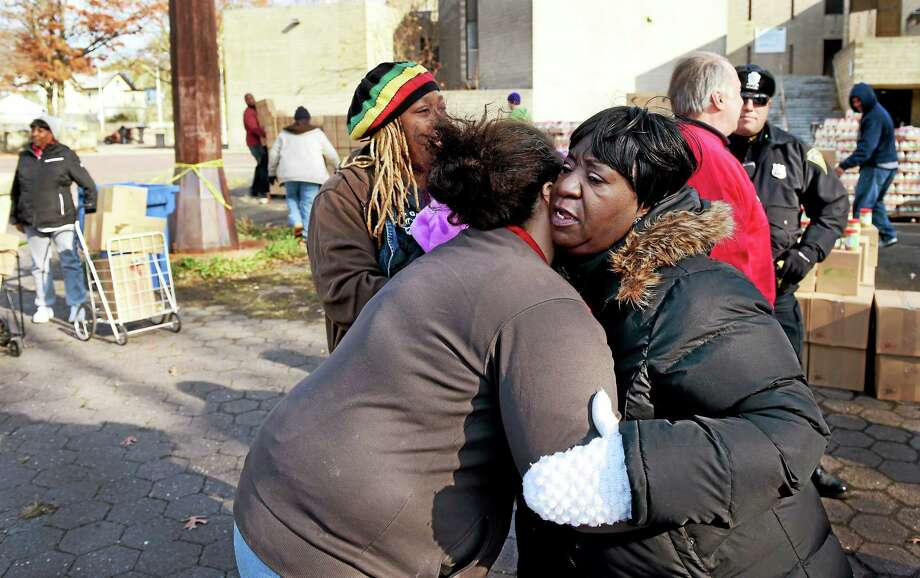 Pastor Brenda Adkins of Divine Will Fellowship is hugged, right, as boxes of food and other essential items from Feed the Children are distributed to families in need Thursday at the former Community Dixwell Avenue Q House in New Haven. Photo: Peter Hvizdak — New Haven Register    / ©2014 Peter Hvizdak
