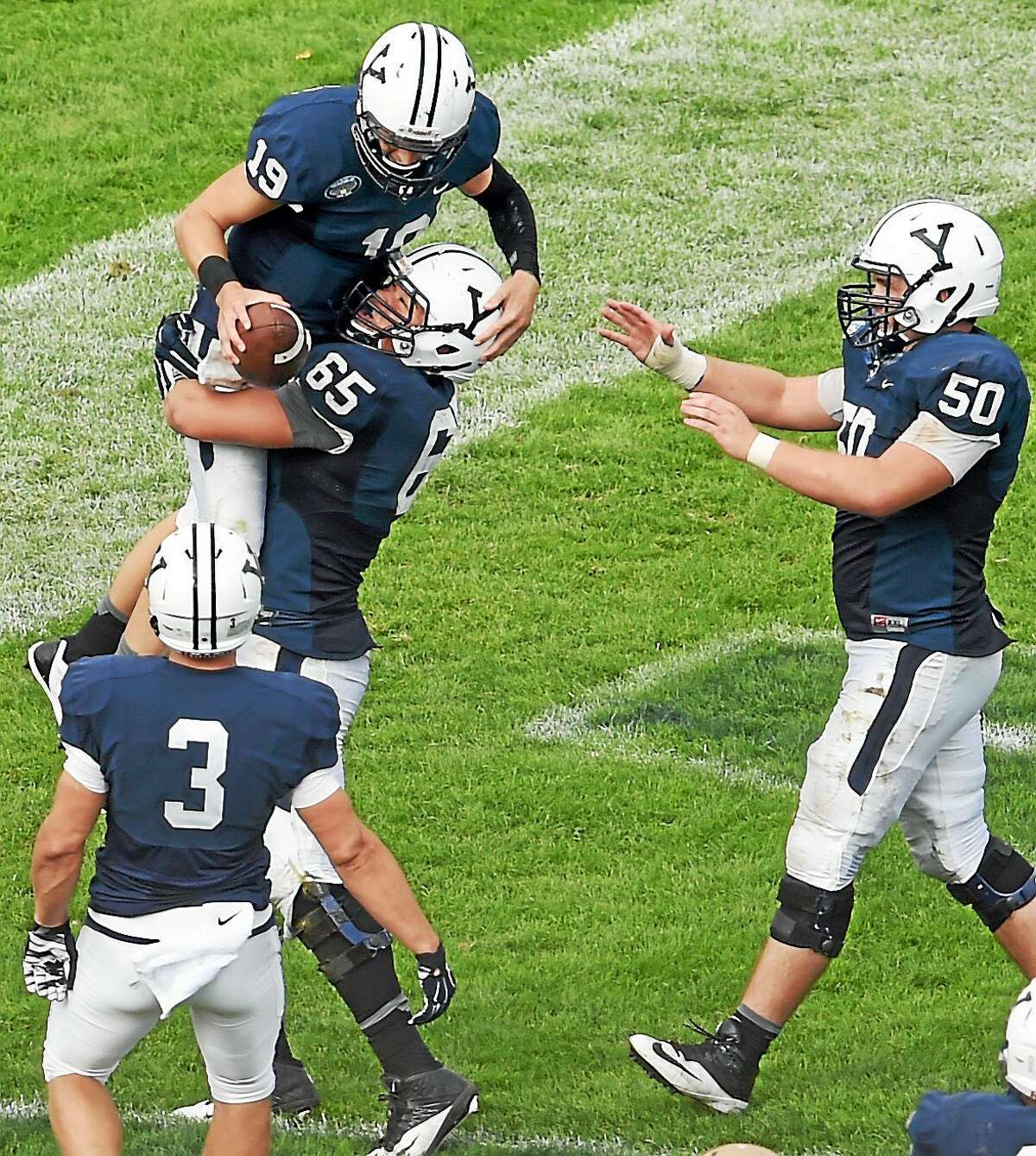 Yale quarterback Morgan Roberts is lifted up in the end zone by teammate Khalid Cannon after Roberts scored a touchdown during the fourth quarter of the Bulldogs' 54-43 win over Lehigh on Saturday at Yale Bowl.