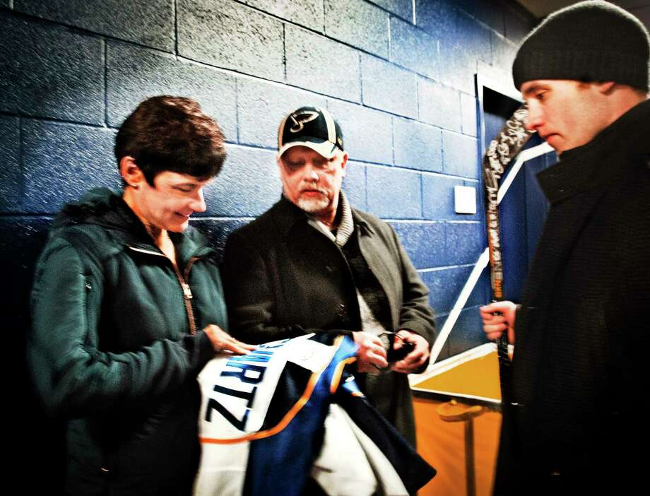 Carol and Rick Schwartz look at the St. Louis Blues jersey given to them by their son, Jaden, a player on the team. The jersey bears the name of their daughter, Mandi Schwartz, who played hockey for Yale. Photo: Melanie Stengel — New Haven Register