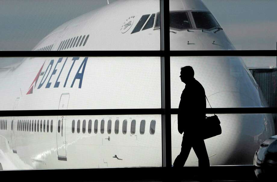 FILE - In this file photo made Jan. 21, 2010, a passenger walks past a Delta Airlines 747 aircraft in McNamara Terminal at Detroit Metropolitan Wayne County Airport in Romulus, Mich. Delta Air Lines on Tuesday, July 22, 2014 canceled all flights to Israel until further notice, citing reports that a rocket landed near Tel Aviv's Ben Gurion Airport. (AP Photo/Paul Sancya, File) Photo: AP / AP