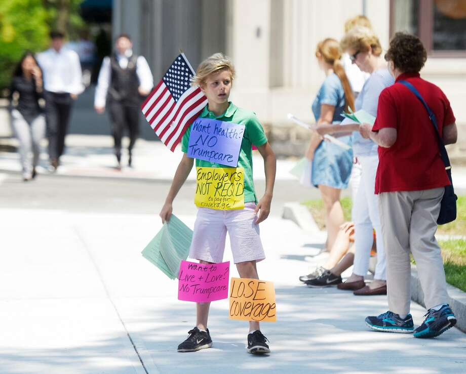 Tyler Fahey, 11, shows an array of signs during a June 27 protest in Greenwich, Conn., against Republican plans to repeal and replace the Affordable Care Act. Photo: Tyler Sizemore, Hearst Connecticut Media