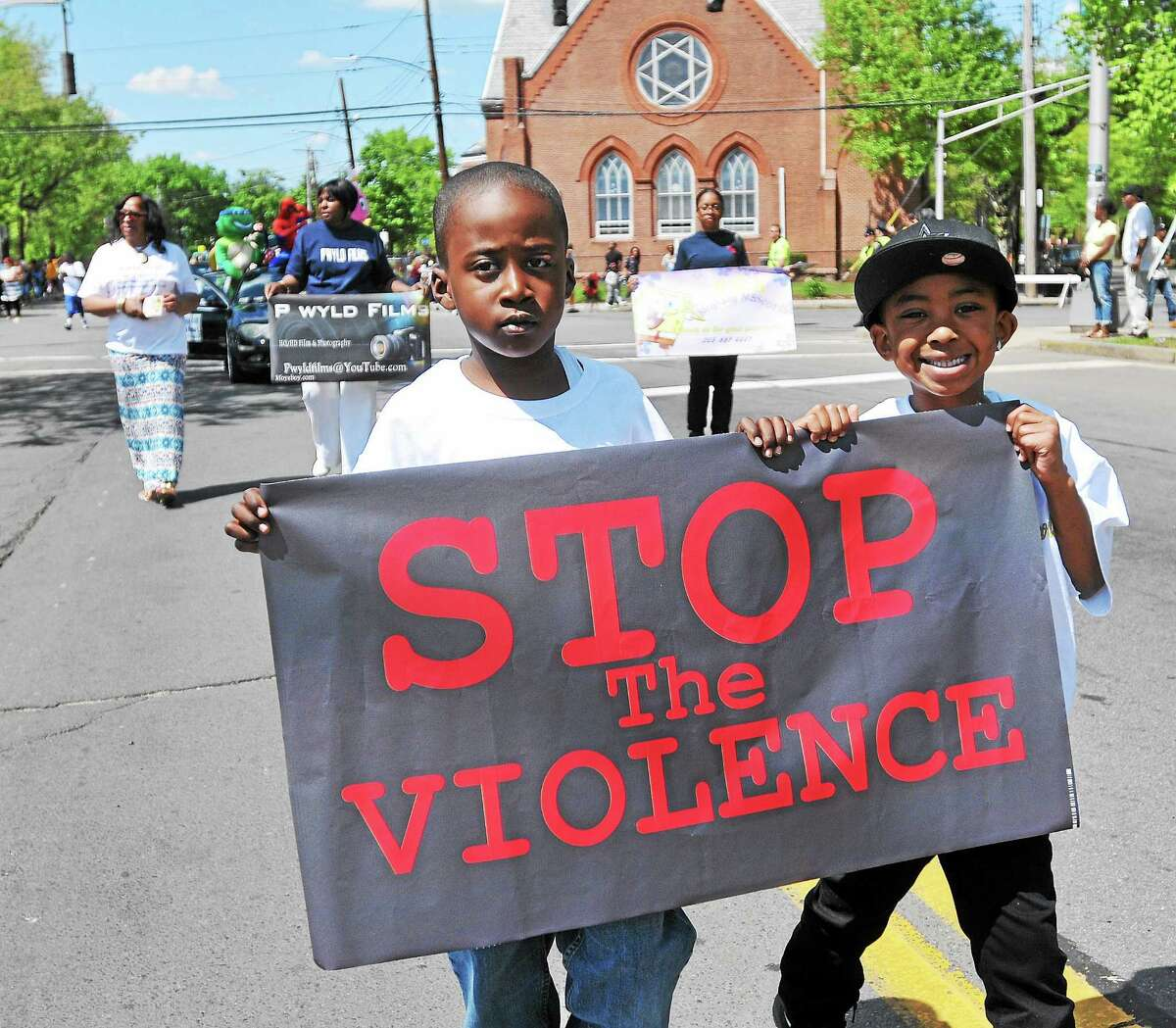 Jerris Moye Jr., left, and his cousin Jayden Moye-Avery carry an anti-violence sign in the annual Freddie Fixer parade along Dixwell Avenue, from Hamden to New Haven.