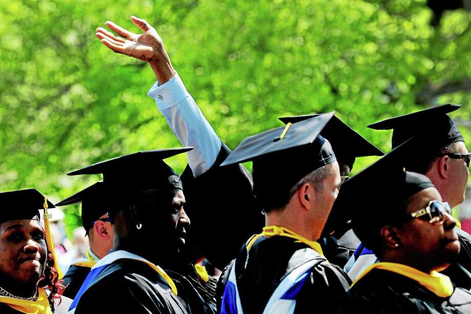 (Peter Hvizdak - New Haven Register)  A graduate waves to his family and friends during the Albertus Magnus College Ninety-First Commencement Exercises Sunday, May 18, 2014 at Albertus Magnus College in New Haven. Photo: New Haven Register / ©Peter Hvizdak /  New Haven Register