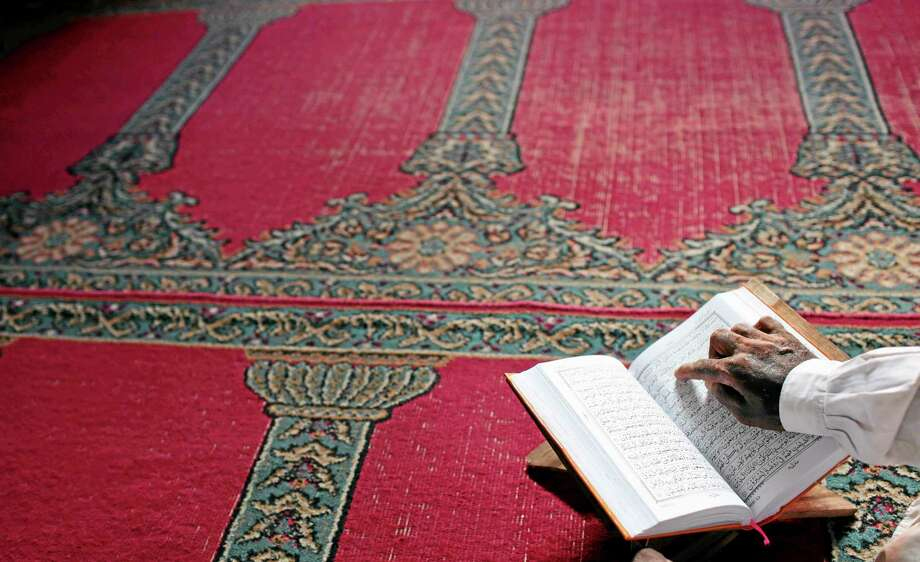 A Bangladeshi Muslim reads the holy Quran at a mosque during Ramadan in Dhaka, Bangladesh, Thursday, July 17, 2014. Muslims throughout the world are marking the month of Ramadan, during which they fast from dawn till dusk. (AP Photo/A.M. Ahad) Photo: AP / AP