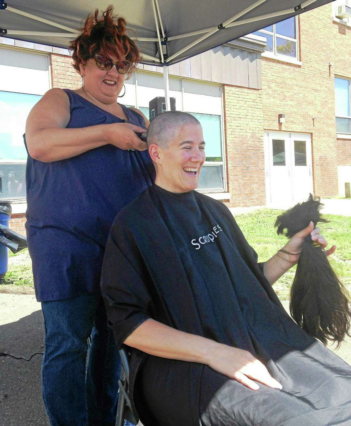 Joanne Poffenberger, a West Haven High School science teacher, holds the hair that stylist Teddi McKenna, of Teddi & Archell a Salon in West Haven, shaved off her head at Sundayís Westie Day of Hope fundraiser at West Haven High School.