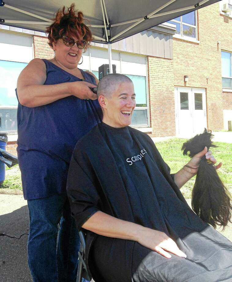 Joanne Poffenberger, a West Haven High School science teacher, holds the hair that stylist Teddi McKenna, of Teddi & Archell a Salon in West Haven, shaved off her head at Sundayís Westie Day of Hope fundraiser at West Haven High School. Photo: (Contributed Photo - West Haven Board Of Education)