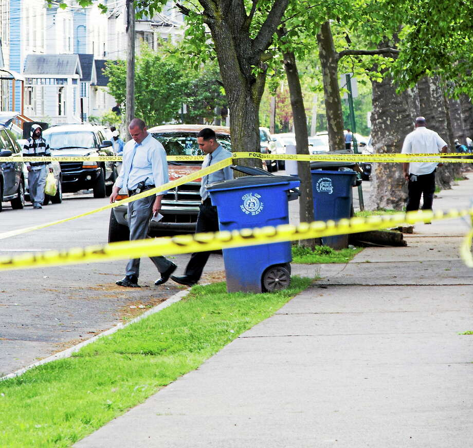 New Haven police detectives canvass West Ivy Street after a 19-year-old was wounded in an apparent drive-by shooting Monday evening. Photo: Rich Scinto — New Haven Register