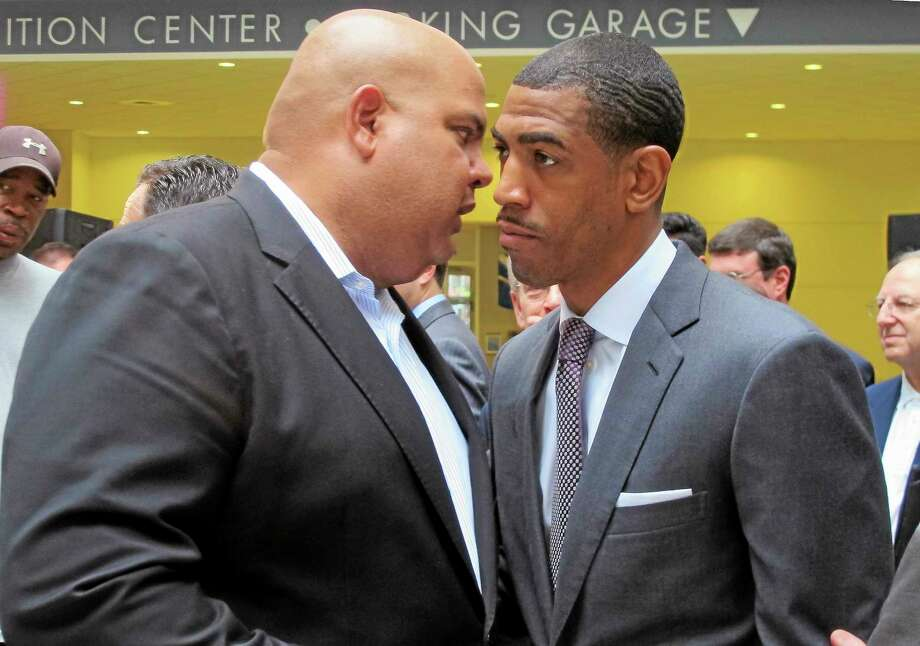 UConn athletic director Warde Manuel, left, and men's basketball coach Kevin Ollie speak after a news conference in Hartford on Friday to discuss the choice of the XL Center as the site of the 2015 American Athletic Conference tournament. Manuel and Ollie both said they are continuing to negotiate a new contract for the coach and have no deadline. Photo: Pat Eaton-Robb — The Associated Press   / AP