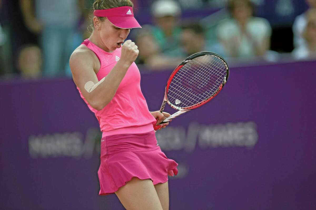 Romania' Simona Halep celebrates after winning a point against Italy's Roberta Vinci in the singles final match of a WTA Bucharest Open women's tennis tournament in Bucharest, Romania, Sunday, July 13, 2014. Halep defeated Vinci in two sets to win the tournament.(AP Photo/Vadim Ghirda)