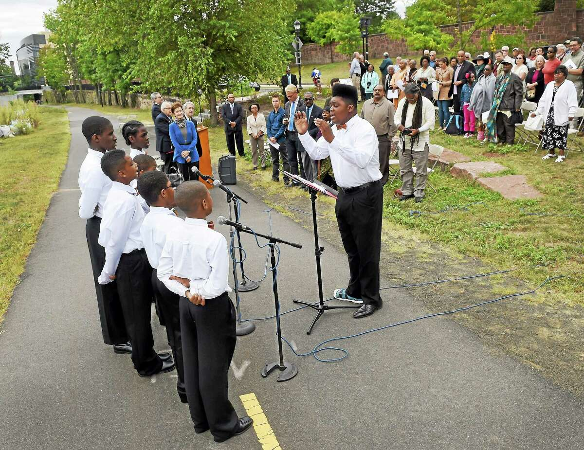 """Donijah Collier, youth director of the Unity Boys Choir leads the singing group during the William Lanson Plaza Dedication ceremony Saturday, September 13, 2014 on the Farmington Canal behind the Yale Health Center in New Haven. A New Haven entrepreneur, Lanson, born in 1771 and died 1851, was an African-American, who, in 1840, """"built a retaining wall for the harbor basin of the newly planned Farmington Canal"""", according to the ceremony program."""