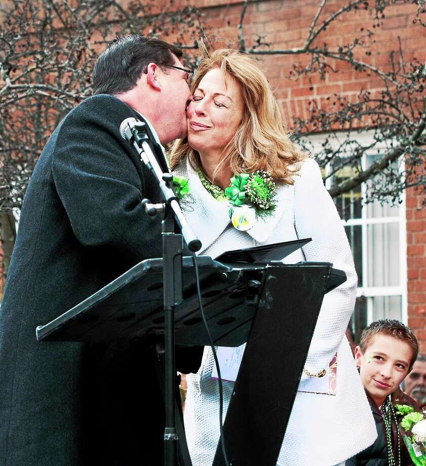 Dorinda Keenan Borer, right, gets a kiss from West Haven Mayor Edward O'Brien during ceremonies honoring her as Irishwoman of the Year Monday. Looking on is Borer's son, Drew, 12. Photo: Melanie Stengel — New Haven Register       / MELANIE STENGEL