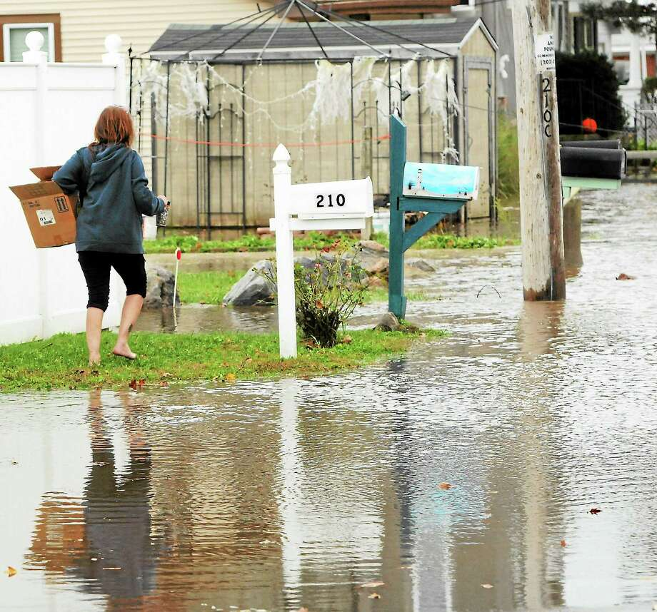 A woman looking for her cat returns to her home facing the water on Cosey Beach Avenue as Hurricane Sandy from Long Island sound hits the  Cosey Beach area of  East Haven, Connecticut October 29, 2012. Photo by Peter Hvizdak / New Haven Register Photo: New Haven Register / ©Peter Hvizdak /  New Haven Register