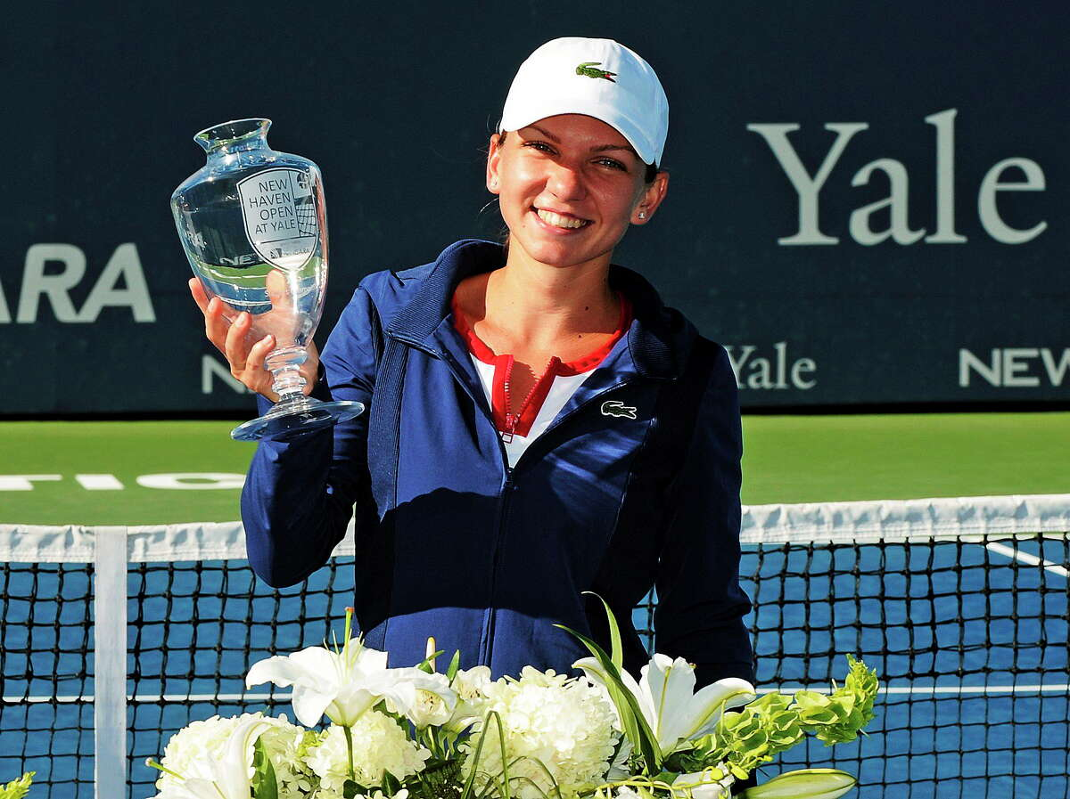 Simona Halep holds the championship trophy after her 6-2, 6-2, victory over Petra Kvitova in the final of the New Haven Open on Aug. 24, 2013.