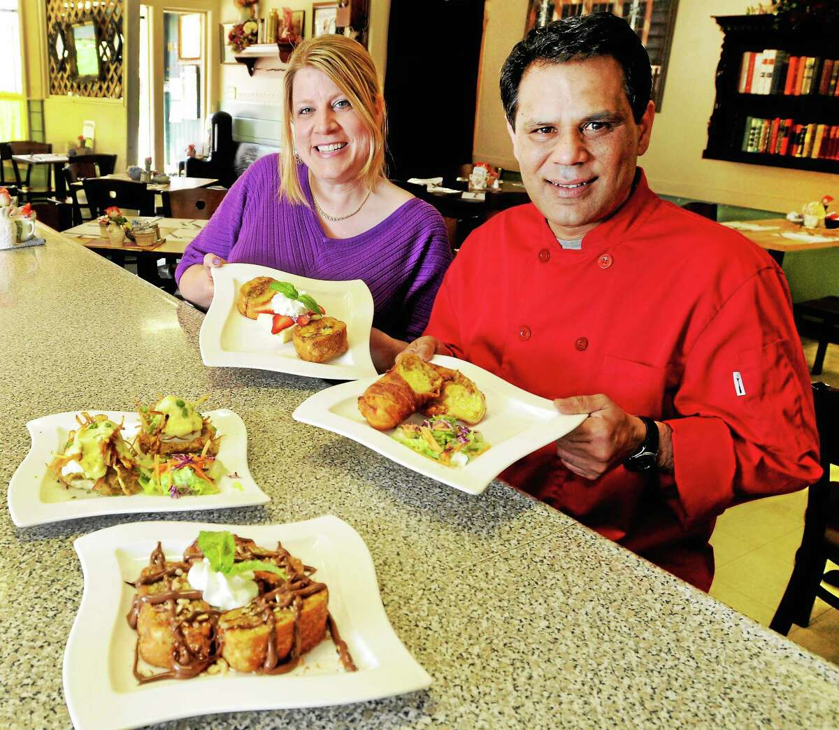 """Michelle and Amer Lebel show off four popular dishes, clockwise from top, right, with Amer holding his South India spiced pulled duck wrapped in a bacon layered tortilla with scrambled eggs and mild cheese; banana-stuffed French toast with Nutella and toasted almond; """"South African Hash"""" of spicy beef and lentil over an English muffin topped with poached eggs, crispy potatoes and Bearnaise sauce; and Michelle holding the """"Trio,"""" an apple cinnamon, raisin, cream cheese stuffed French toast with fresh strawberry and banana with a vanilla cake soaked in sweet cream with strawberries."""