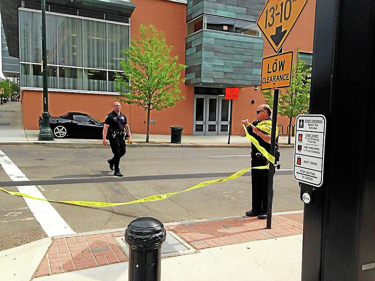 Police officers take down caution tape from an intersection after streets were blocked for the investigation of a suspicious suitcase left near College and George streets. The suitcase was reportedly found to contain clothing.