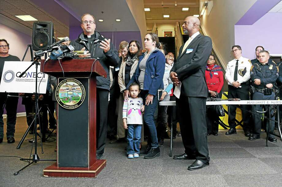 The Rev. James Manship, left, co-chairman of CONECT, speaks at a press conference announcing a joint effort with Do Not Stand Idly By to leverage the purchasing power of state and local governments to pressure gun manufacturers to adopt gun safety technology, Monday at the Morton Government Center in Bridgeport. Photo: Arnold Gold — New Haven Register