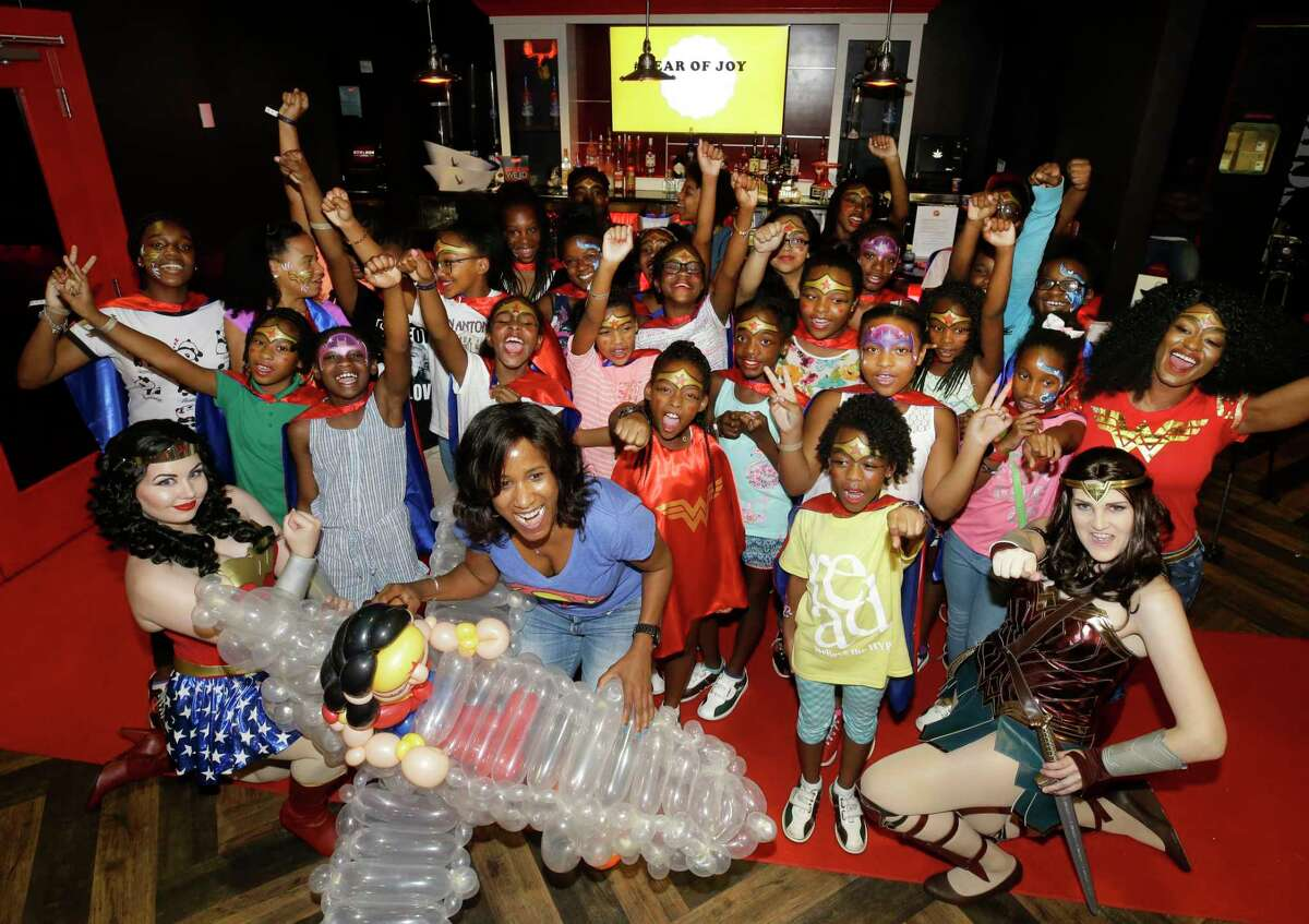Joy Sewing, Houston Chronicle Fashion and Beauty Editor, front center, poses in a group photo during a Wonder Woman Bowling Party for 30 area girls ages 7 to 12 held at Bowlmor, 925 Bunker Hill Road, as part of her #YearOfJoy project Monday, July 24, 2017, in Houston.