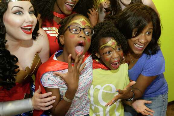 Joy Sewing, Houston Chronicle Fashion and Beauty Editor, right, poses with girls and characters during a Wonder Woman Bowling Party for 30 area girls ages 7 to 12 held at Bowlmor,  925 Bunker Hill Road, as part of her #YearOfJoy project Monday, July 24, 2017, in Houston.