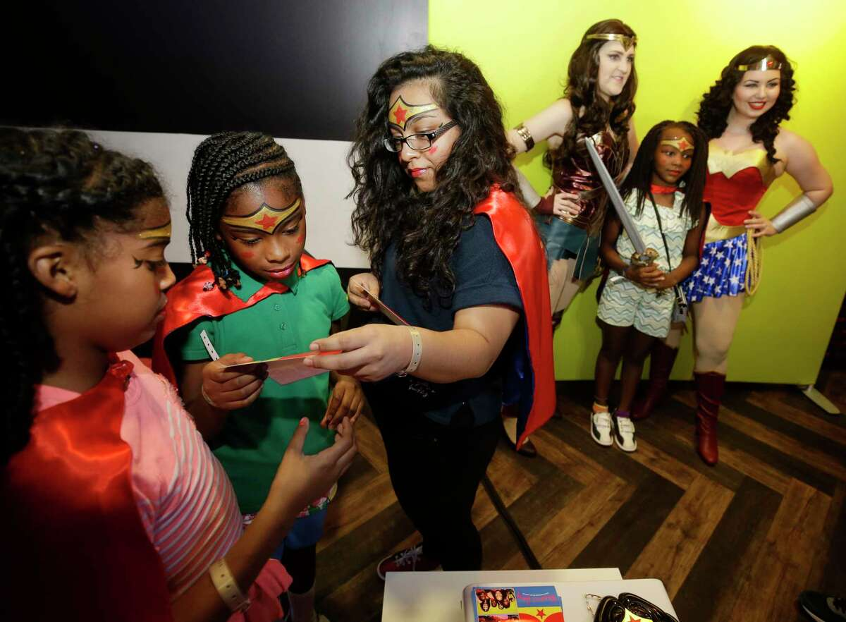 Carmen Ford, 10, left, Don Coleman, 10, and Karen Lopez, 17, third from left, look at their photos as Zoe Mayes, 9, in background, has her photo taken during a Wonder Woman Bowling Party for 30 area girls ages 7 to 12 held at Bowlmor, 925 Bunker Hill Road, hosted by Joy Sewing, Houston Chronicle Fashion and Beauty Editor, as part of her #YearOfJoy project Monday, July 24, 2017, in Houston.