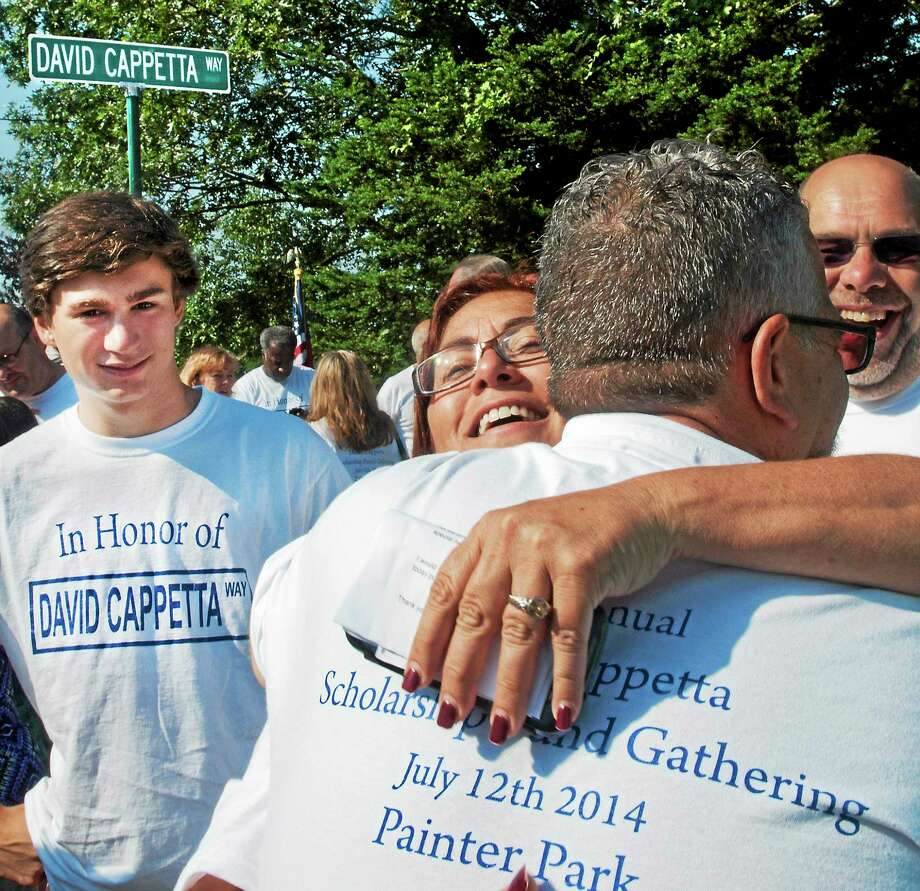 David Cappetta of West Haven, left, son of the late official, looks on Saturday as his aunt, Donna Craig, hugs a friend, Ron Sacco, during a fundraiser in honor of the late, elder Cappetta. The event was held at Painter Park in West Haven. Cappetta died after a long bout with muscular distrophy. In the background is a street sign named for Cappetta. Photo: Melanie Stengel — New Haven Register