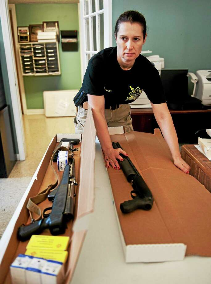 New Haven Police Officer Donna Aponte, with an AK46, left, and a Mossberg 500 obtained at the gun buyback held Saturday at Radio AMOR. Photo: Melanie Stengel — New Haven Register