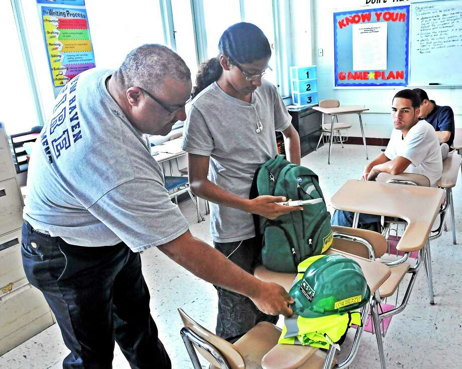 New Haven fire Lt. Gary Tinney looks over a Community Emergency Response Team equipment bag with James Hillhouse High School sophomore Jacob Burnett during a CERT training class at the school. Photo: Peter Casolino — New Haven Register