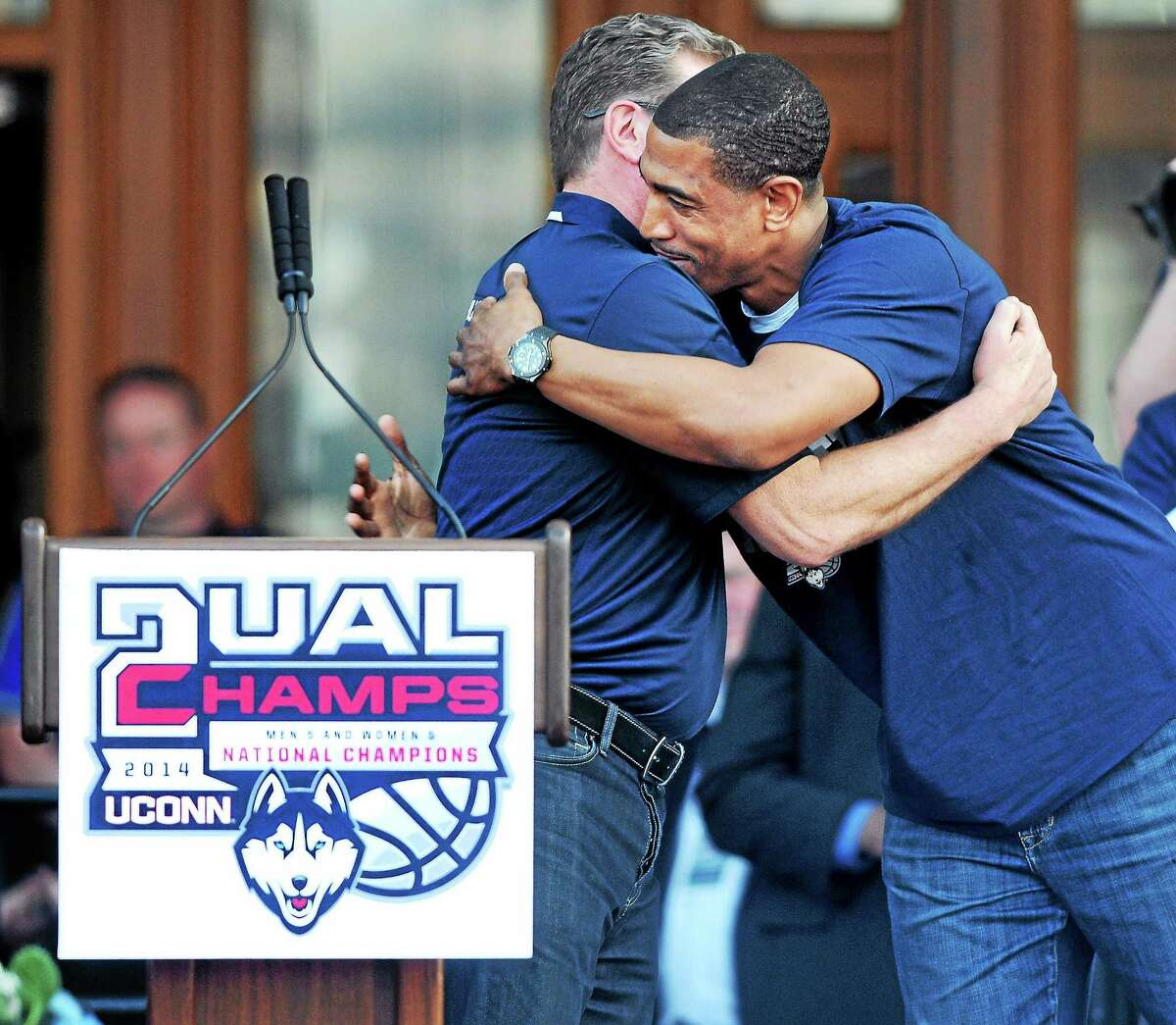 In this April 13, 2014 file photo, UConn women's basketball coach Geno Auriemma, left, hugs UConn men's basketball coach Kevin Ollie at a victory rally in front of the Capitol Building in Hartford.