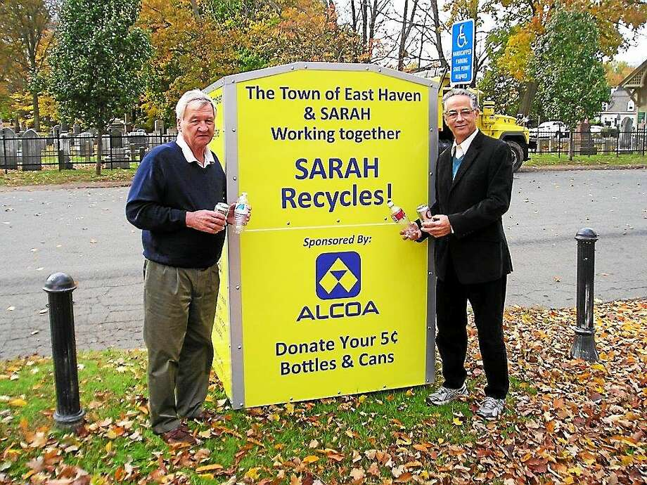 From the left, Jim Lamb, manager of business development for SARAH Inc. and East Haven Mayor Joseph Maturo, Jr. as they recycle into one of the new bins. Photo: Journal Register Co.