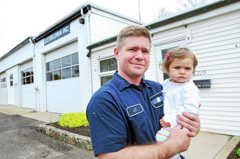 J.P. Sullivan, vice president and fourth generation of J.J. Sullivan Inc., with his 16-month-old daughter, Maile, in front of the family business in Guilford last week. Photo: ARNOLD GOLD — NEW HAVEN REGISTER