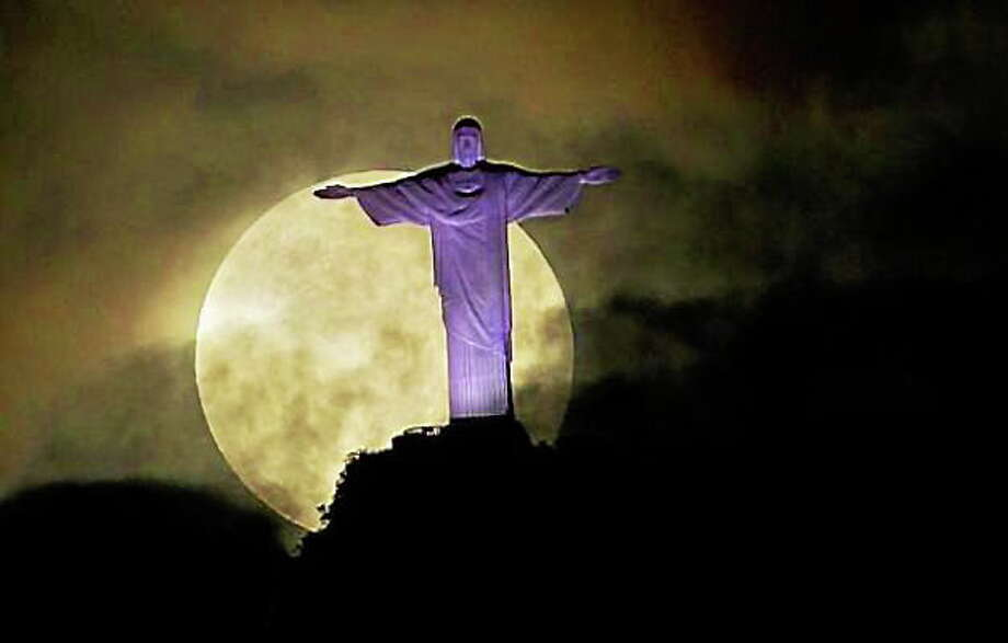"""The tremendous size of the """"supermoon"""" could be appreciated as it appeared last May behind the colossal statue of Christ of the Andes in Brazil. Photo: AP File Photo"""