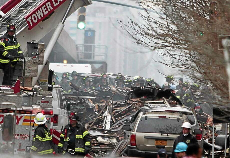 Firefighters continue to investigate and remove debris from an explosion in Harlem, Wednesday, March 12, 2014 in New York. A gas leak triggered an explosion that shattered windows a block away, rained debris onto elevated commuter railroad tracks close by, cast a plume of smoke over the skyline and sent people running into the streets. (AP Photo/Bebeto Matthews) Photo: AP / AP