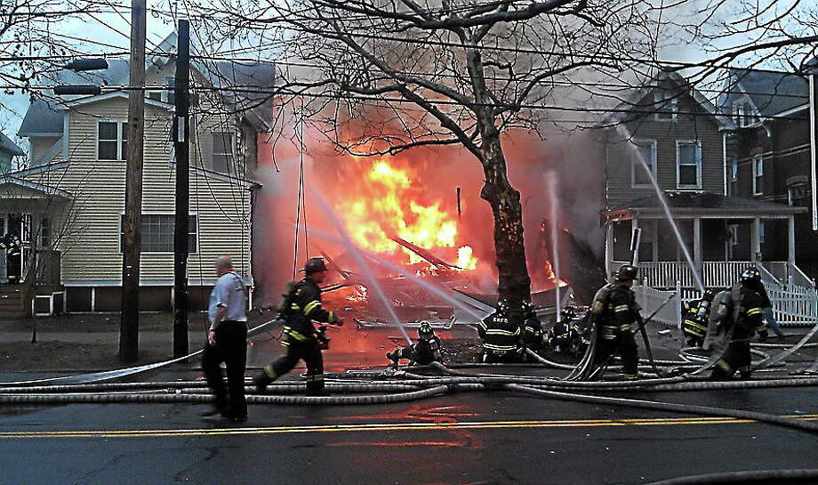 New Haven firefighters aim water at the fiery hole where a home used to stand on Howard Avenue Saturday morning, March 3, 2012, while trying to protect nearby homes from burning. File photo. Photo: Journal Register Co.
