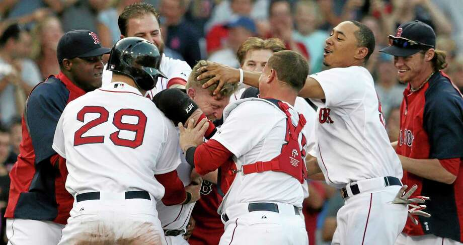 Red Sox pinch hitter Mike Carp, center is congratulated by teammates after his walk-off RBI single Thursday against the White Sox. Photo: Charles Krupa — The Associated Press   / AP