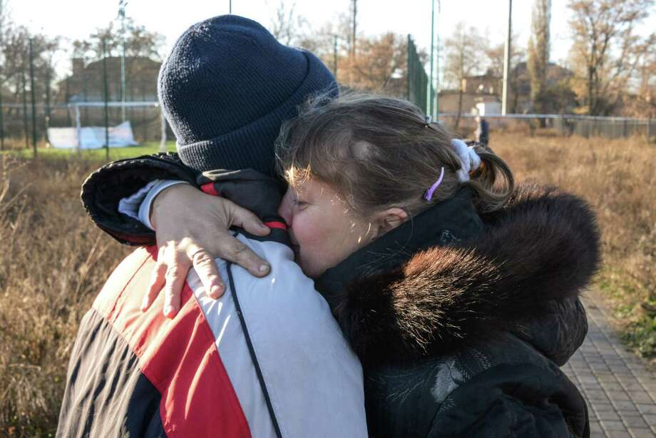 Unidentified parents of the killed and injured children embrace at the place of the tragedy at a football pitch in Donetsk, Eastern Ukraine on Thursday, Nov. 6, 2014, where shelling took place Wednesday. Two bloodied coats lay on the school pitch early Thursday morning, a day after an artillery strike killed two teenagers and injured four more as they were playing football. The attack on the high school is just one example of the blatant violations of the September cease-fire between the rebels and the Ukrainian government which have become daily routine in the past weeks. (AP Photo/ Mstyslav Chernov) Photo: AP / AP