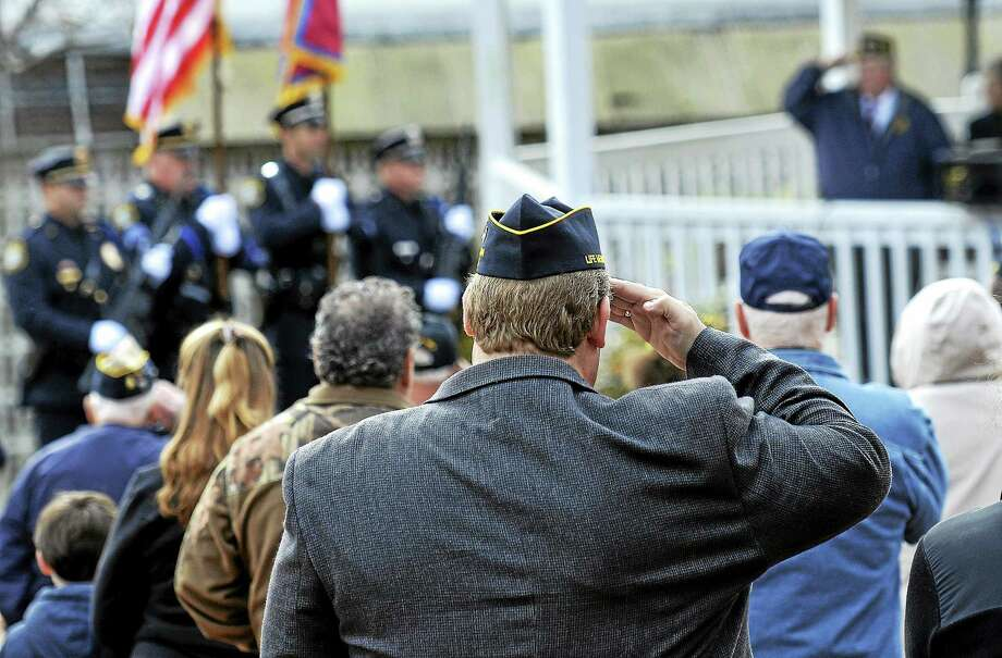 In this 2013 file photo, veterans salute as they honor those who sacrifice during the annual Veteran's Day observance ceremony on the Derby Green. Photo: Peter Casolino — New Haven Register