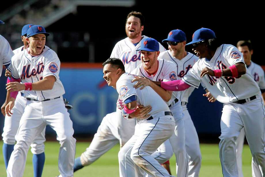 The Mets' Ruben Tejada, center, gets a hug from Zack Wheeler as he is mobbed by teammates after hitting a game-winning RBI single during the 11th inning Sunday. Photo: Jason DeCrow — The Associated Press   / FR103966 AP
