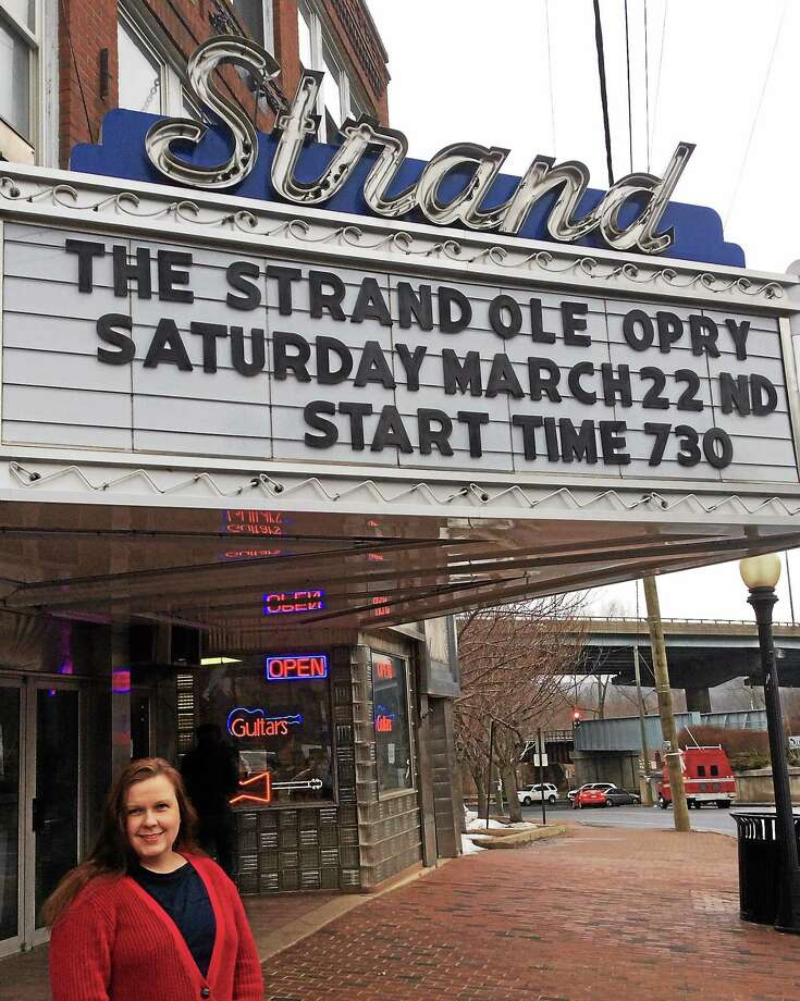 Kimberly Dulka, owner of the All-American Valley General Store in downtown Seymour, in front of The Strand Theater's marquee announcing a concert to support the theater. Patricia Villers/Register Photo: Journal Register Co.
