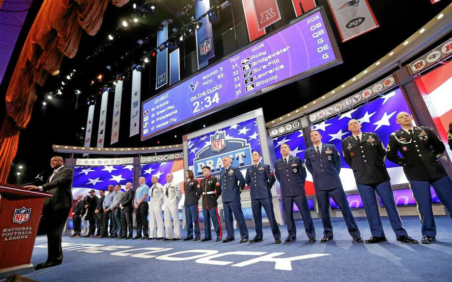 Members of the United States military line the stage as the Chicago Bears' third-round pick, Will Sutton of Arizona State, is announced during the 2014 NFL Draft, Friday. Photo: Jason DeCrow — The Associated Press   / FR103966 AP