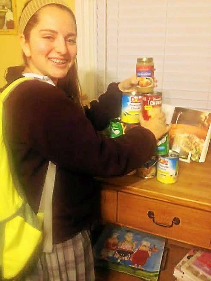 """Emily Fowler, 14, daughter of """"West Haven — The Way It Is"""" co-founder Rich Fowler, with some of the canned goods people have dropped off in advance of this weekend's food and clothing drive. Photo: CONTRIBUTED PHOTO — Rich Fowler"""