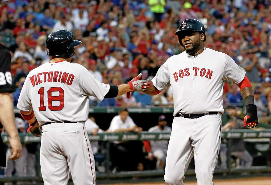 David Ortiz, right, and Shane Victorino congratulate each other after scoring on a hit by Jonny Gomes against the Texas Rangers during the fourth inning Saturday. Photo: Jim Cowsert — The Associated Press   / FR170531 AP