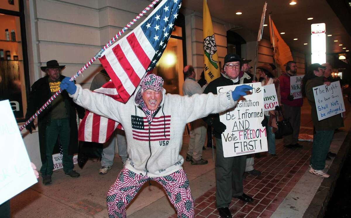 Tea party supporters, including Zeqir Berisha of Waterbury, protest on College Street outside the Owl Shop Thursday in New Haven, where top GOP leaders met for a private fundraiser.