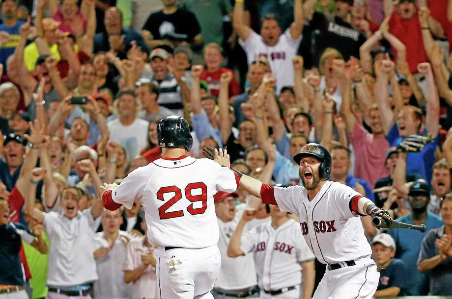 The Red Sox's Daniel Nava (29) is greeted by teammate Dustin Pedroia as he scores the winning run on Brock Holt's single in the ninth inning against the Chicago White Sox at Fenway Park Wednesday. The Red Sox won 5-4. Photo: Elise Amendola — The Associated Press   / AP